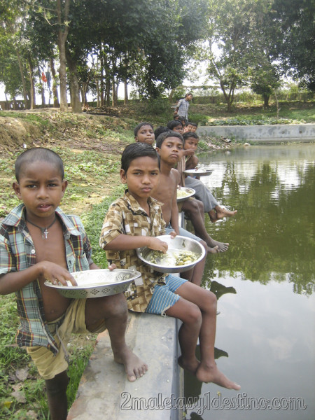 Niños indios comiendo arroz junto al estanque