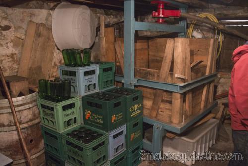 Prensa de madera y botellas de sidra