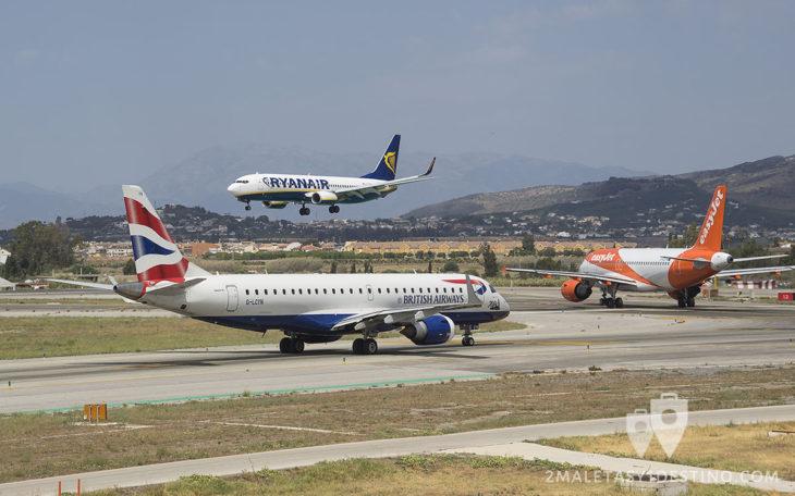 Avión de Ryanair aterrizando y easyJet y British Airways esperando